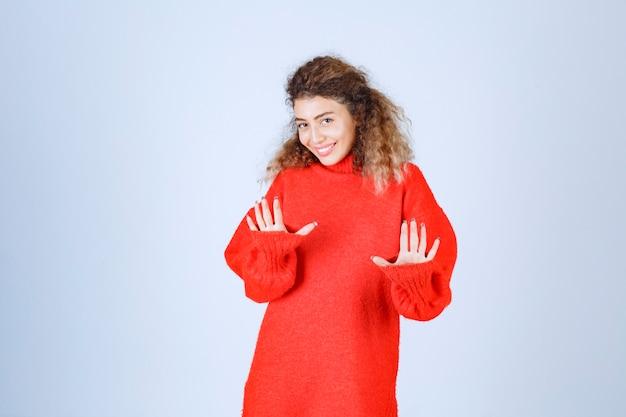 Donna in una camicia rossa che ferma qualcosa.