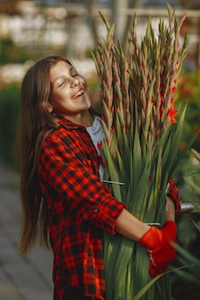 Woman in a red shirt. worker with flowerpoots. daughter with plants