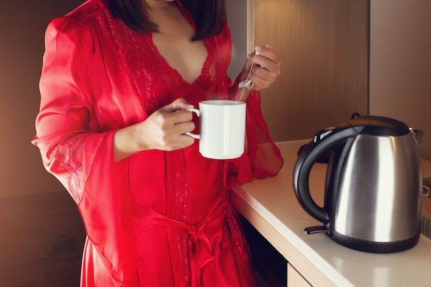 A woman in a red silk nightgown and luxurious robes making hot tea in the kitchen at night