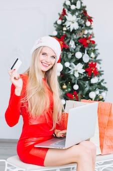 Woman in red sitting with laptop and card near christmas tree