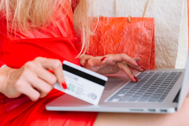 Woman in red sitting with laptop and card near shopping bags
