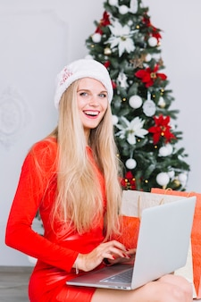 Woman in red sitting with laptop near christmas tree