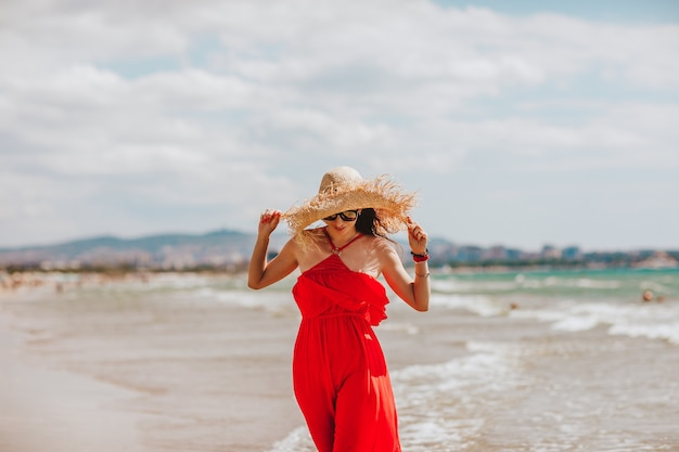 Woman in red summer dress with straw hat and sun glasses walking on the beach