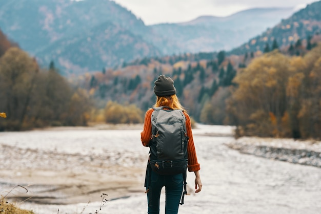 Woman in a red sweater cap with a backpack on the river bank and mountains in the distance