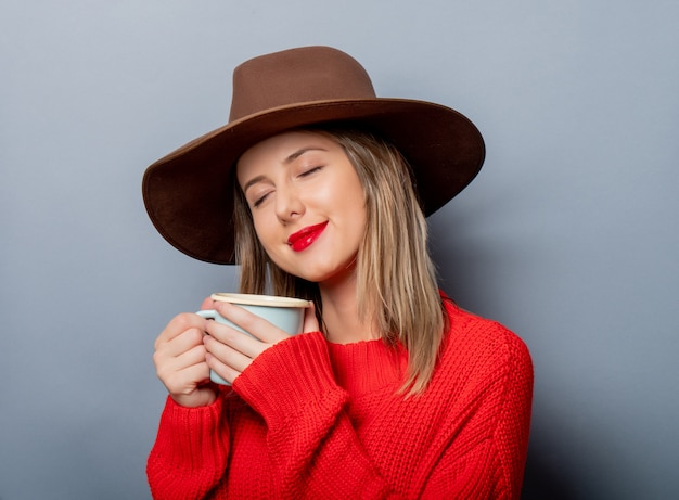 Woman in red sweater and hat with cup of coffee