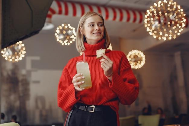 Donna in un maglione rosso. la signora beve un cocktail.