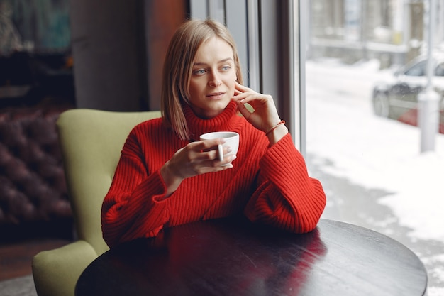 Woman in a red sweater. lady drinks a coffee.