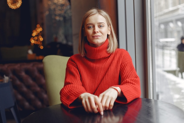 Woman in a red sweater. lady in a restaurant.