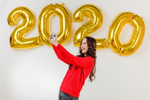 Woman in red sweater taking photos with vintage camera in front of 2020 new year balloons