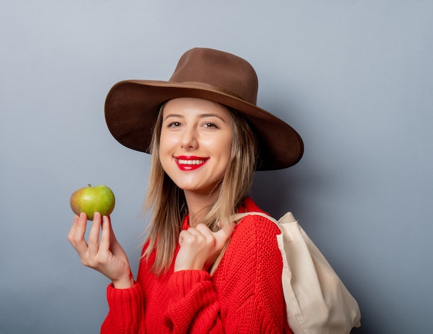 Woman in red sweater with apple and bag