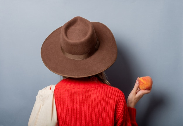 Woman in red sweater with peach and ba