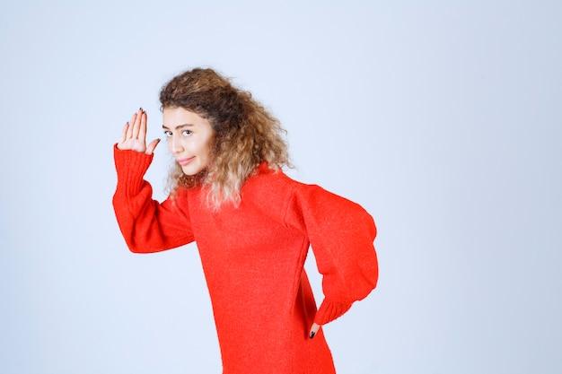 Donna in felpa rossa in fuga dal luogo.