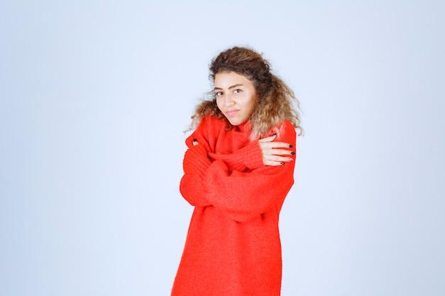 Woman in red sweatshirt feeling cold.