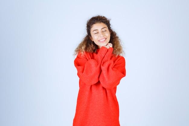 Donna in felpa rossa che dà pose allegre e positive.