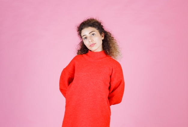 Woman in red sweatshirt giving neutral poses.