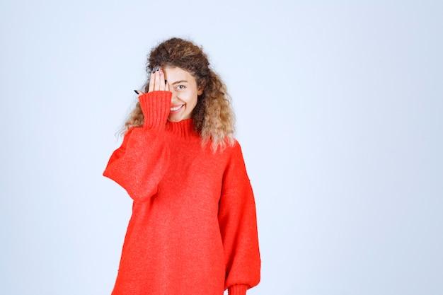 Woman in red sweatshirt looking across her fingers.