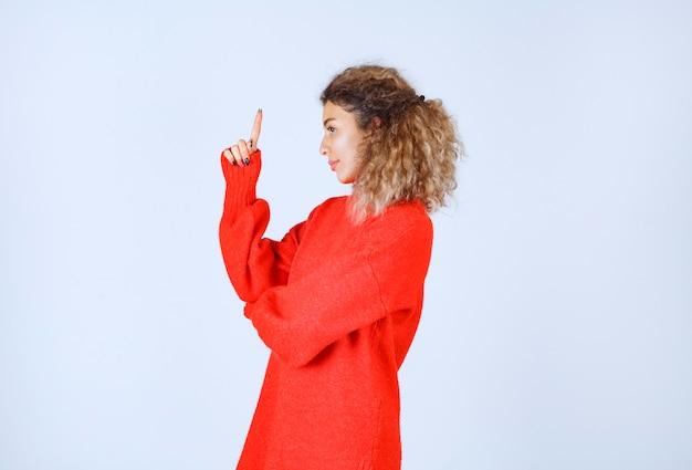 Donna in una felpa rossa che punta su lati diversi.