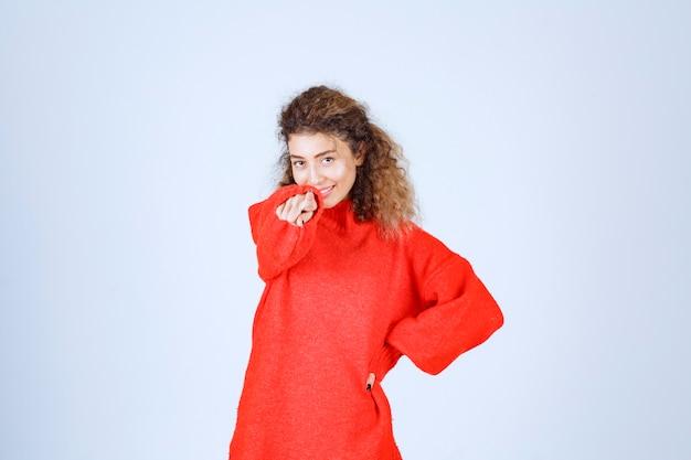 Donna in felpa rossa che indica qualcuno avanti.
