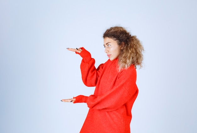 Woman in red sweatshirt showing the estimated amount or size of a product.