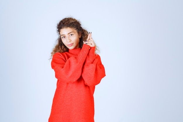 Woman in red sweatshirt showing gun sign.