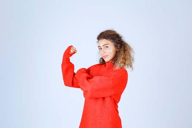 Donna in felpa rossa che mostra il pugno e significa il suo potere.