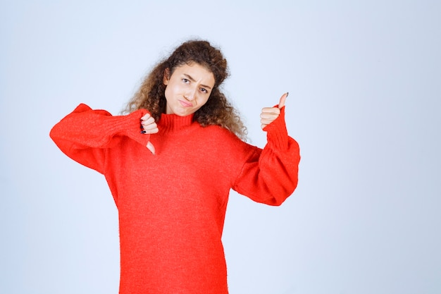 Woman in red sweatshirt showing thumb up and down signs.