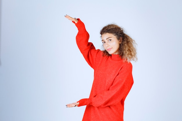 Woman in red sweatshirt showint the measures of an object.