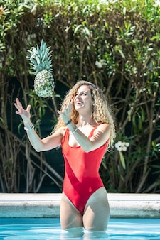Woman in a red swimsuit throwing a pineapple in the air into a pool