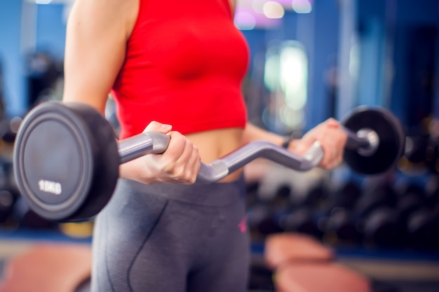 Woman in red top with short blond hair training bicep in gym. people, fitness and lifstyle concept