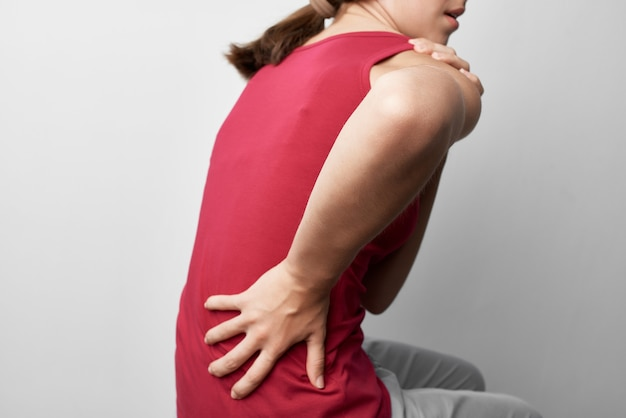Woman in red tshirt holding her back health problems rheumatism medicine lifestyle