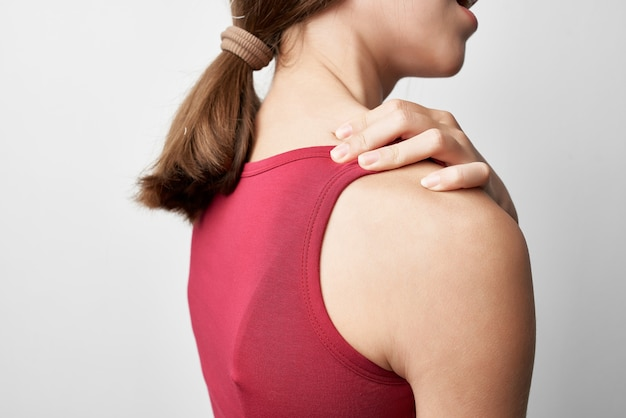 Woman in red tshirt in the shoulders health problems arthritis treatment