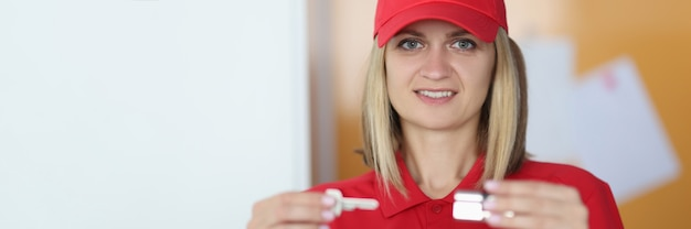 Woman in red uniform holds a key and lock in her hands.