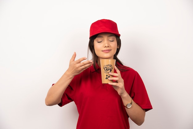 La donna in uniforme rossa annusa il caffè dell'aroma in tazza marrone.