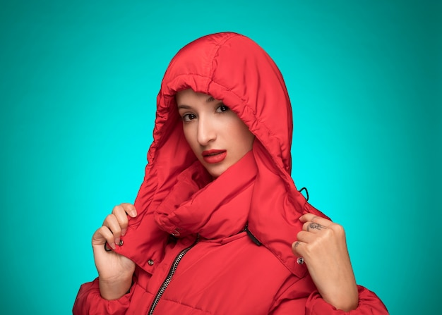 Woman in red winter hooded jacket blue background