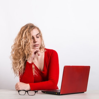 Woman in red, working remotely at the computer on white.