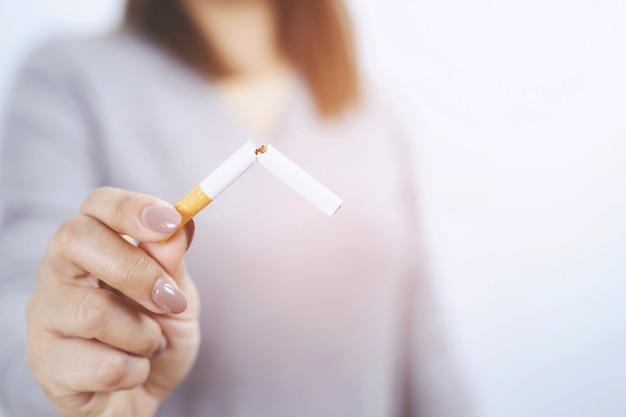 禁煙と健康的なライフスタイルのためのタバコの概念を拒否する女性。または禁煙キャンペーンの概念。