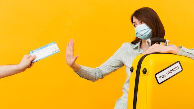 Woman rejecting a plane ticket while wearing e medical mask