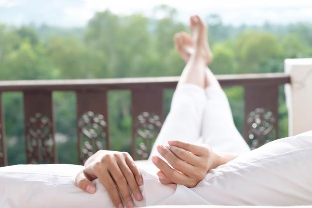 女性はベッドでリラックスし、山の景色を楽しんでいます。