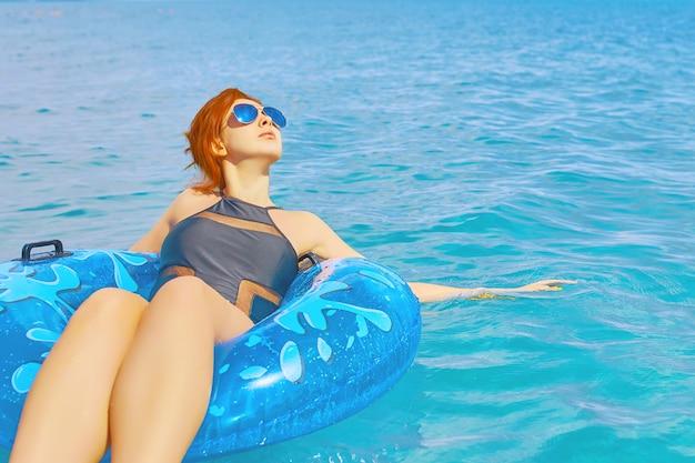 女性は海の水で膨脹可能なリングでリラックスします。