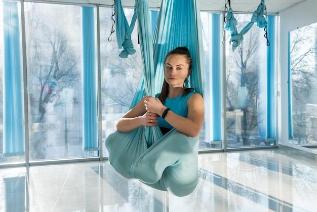 Женщина расслабляется с помощью йоги мух в фитнес-тренировке. fly yoga для здоровья и хорошей формы. мягкий фокус.