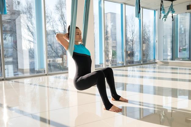 Женщина расслабляется, используя летать йогу в фитнес-тренировке