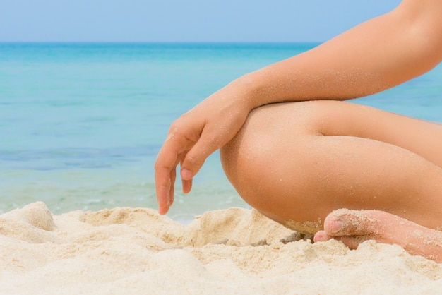 Woman in relaxation on nice beach with sand on body parts. yoga and recreation.