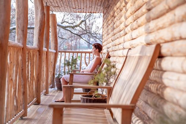 女性は冬に木製の丸太小屋でサウナの後にリラックスします。