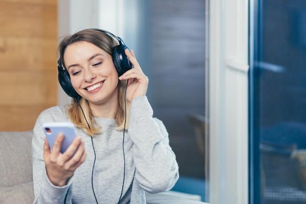Женщина расслабляется дома и слушает музыку в больших наушниках, использует мобильный телефон