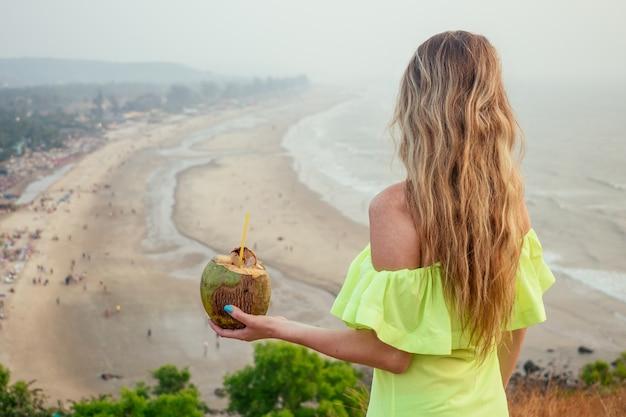 여자는 해변이 내려다 보이는 산 꼭대기 이완