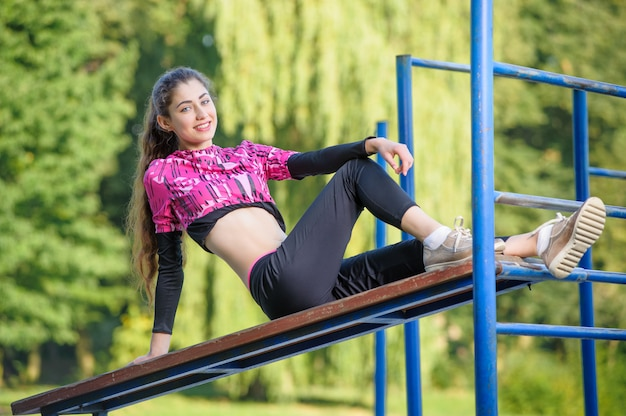 Woman relaxing after fitness exercises on gym bar in park