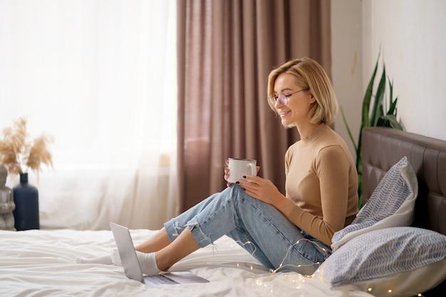 편안 하 고 침실에서 랩톱 컴퓨터를 사용 하여 뜨거운 커피 또는 차 한잔 마시는 여자.