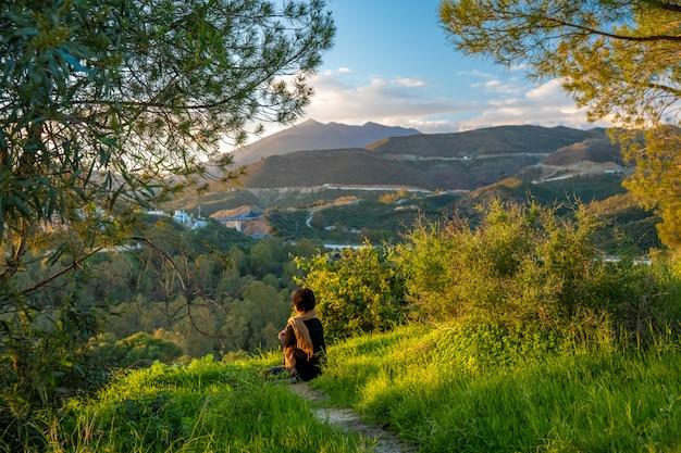 田舎と山々の美しい景色と緑の丘の夕日でリラックスして瞑想の女性