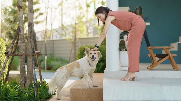 Женщина расслабляющий и играя со своей милой собакой.