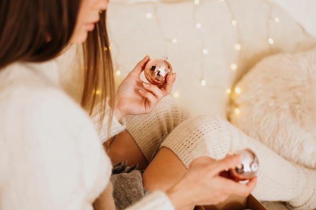 家でリラックスし、装飾的な木のボールを保持している女性